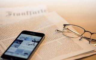 Lunor Brille mit Zeitung und Smartphone